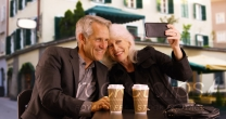 Sweet elderly couple taking selfies outdoors