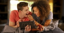 Happy Couple of multiracial friends using tablet handheld device.