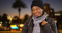 An older black woman in warm clothes downtown at night