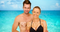 Attractive Caucasian millennial couple standing at the beach smiling at camera