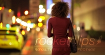 Young black woman in dress waiting for date on sidewalk in Los Angeles