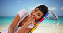 Young black female sitting by the ocean on Caribbean beach talking to camera