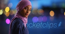 Black female in hijab texting on phone turning to smile at camera in evening