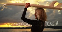 Mature white female surfer holding surfboard over head watching sunset at beach