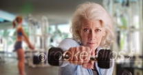 Fit elderly lady at gym working out and looking at camera with determination