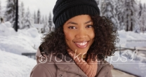 Kind black millennial girl smiling at camera outdoors in snowy setting