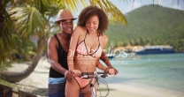 African American couple ride their beach cruiser along the shore in the Caribbean