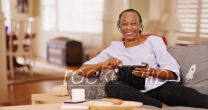 An elderly black woman happily uses her tablet while looking at the camera