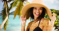 Young white girl in a sun hat poses for a portrait on a Caribbean beach