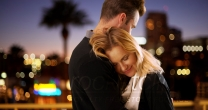 Sweet modern couple hugging outdoors at night