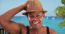 Black man poses happily for a portrait by the beach