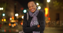 A portrait of an older African American woman laughing in the cold weather on a busy street corner