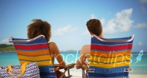 Close-up of couple sitting on beach chairs looking at water horizon.