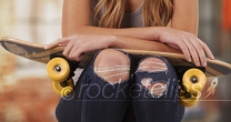 Young white female wearing ripped jeans and a tank top sitting outside building