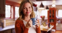 Woman drinking coffee or tea from mug inside contemporary kitchen