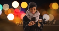 Cute black woman in her 20s texting on phone in urban setting with bokeh lights