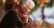 Side portrait of old woman reading concerning text on smartphone at cafe