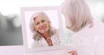Lovely Caucasian senior lady looking at herself in mirror in clean white setting